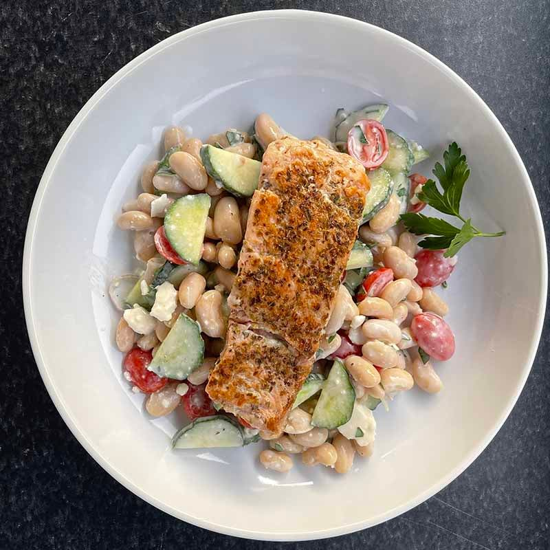 Photo of Salmon over Mediterranean bean salad with feta and yogurt sauce Created by Coach Emily by WW